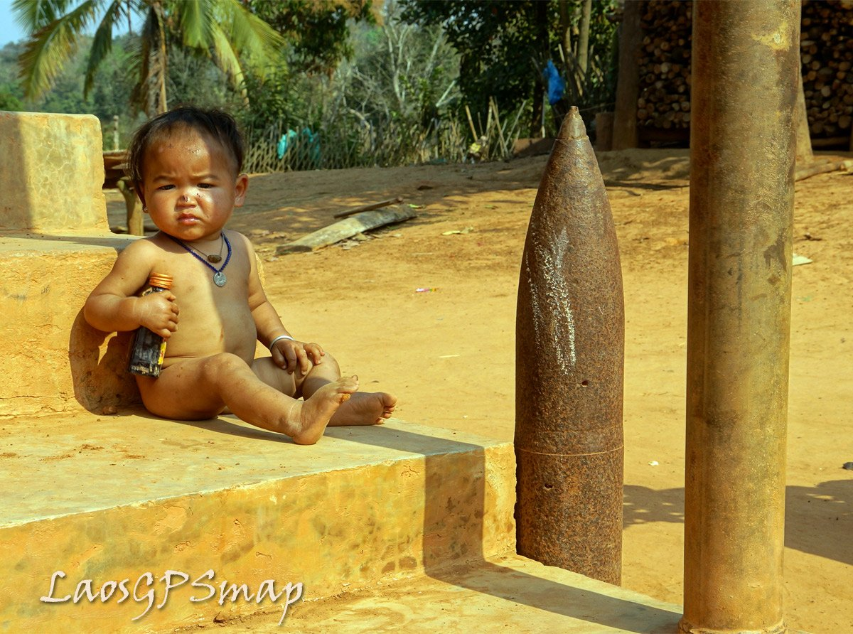 "Ban Tagnong a ""hot"" place on the Ho Chi Minh trail The new generation living with the legacy of the war. A baby sitting on the steps next to an artillery round and a section of the gasoline pipeline that ran the length of the trail"