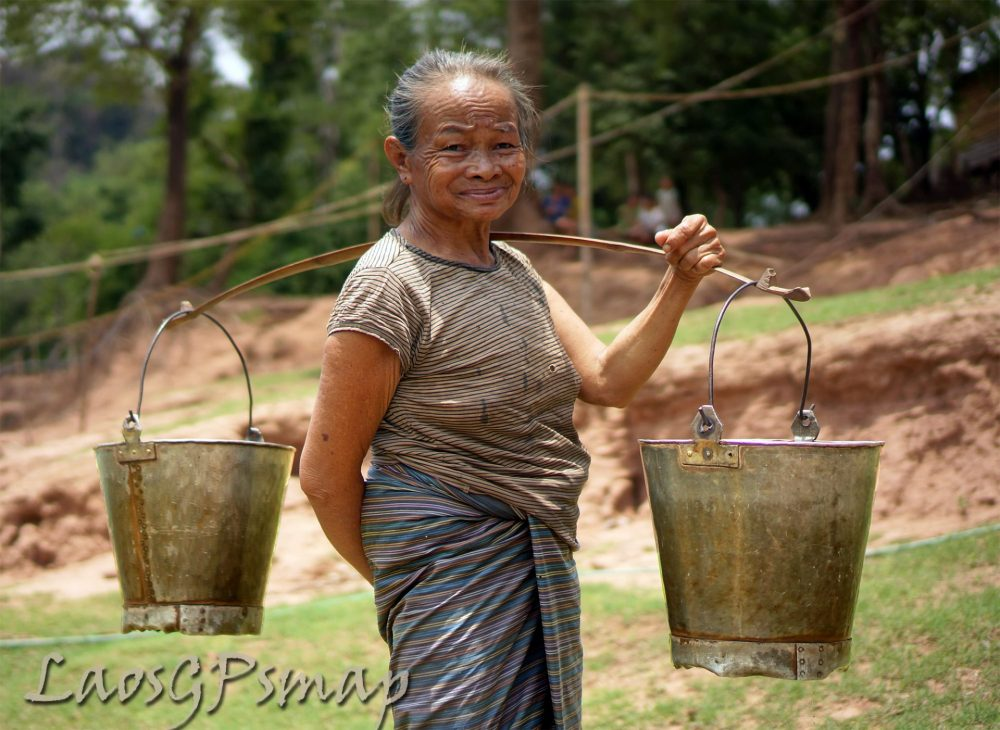 Ho Chi Minh trail, Ban Phanop village women carry water in buckets fabricated from war scraps