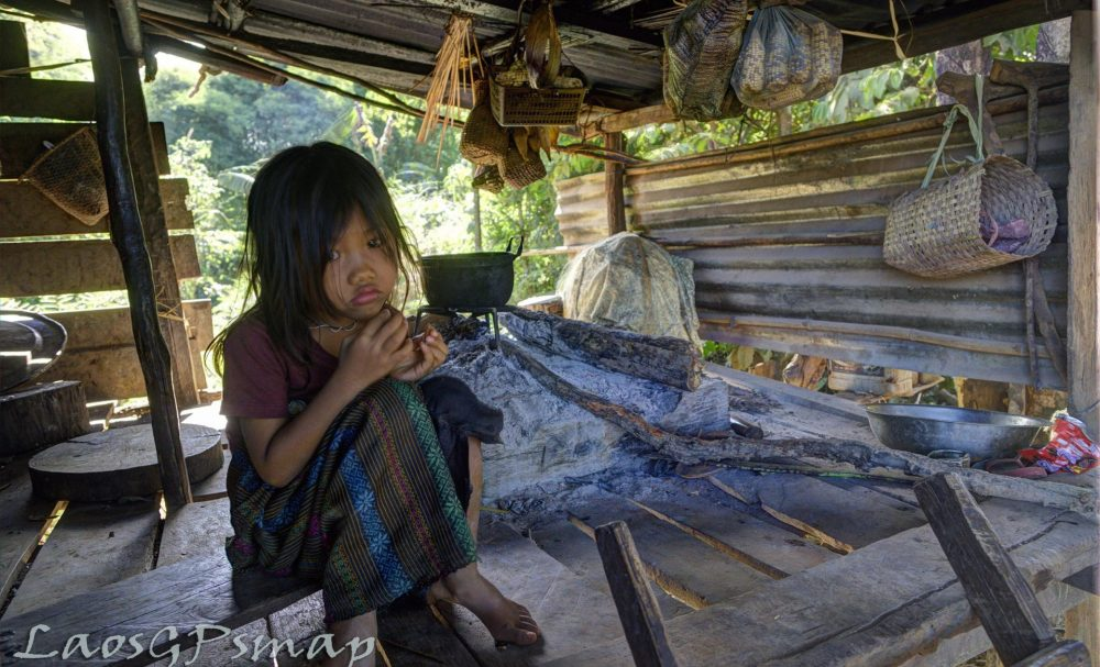 Small child in a village hut, this is the cooking room along side the Ho Chi Minh trail